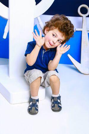 Little captain. Boy plays seaman. Child and sea wheel. Child and yacht mock. Boy posing in studio. Standard-Bild - 129259166