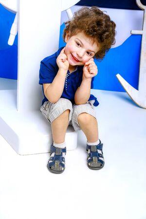 Little captain. Boy plays seaman. Child and sea wheel. Child and yacht mock. Boy posing in studio. Standard-Bild - 129259175