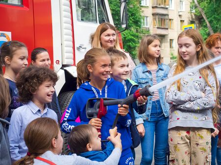 MOSCOW, RUSSIA - AUGUST 07, 2019: Side view of children and parents at a fire station trying a fire hose and sprays water, assisted by a fireman
