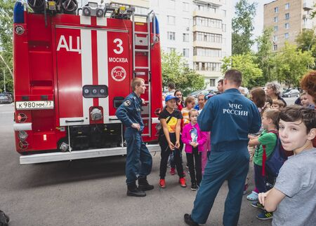 MOSCOW, RUSSIA - AUGUST 07, 2019: Fire station. A fireman explaining his job to children. Fire Station One open family day tour. Редакционное