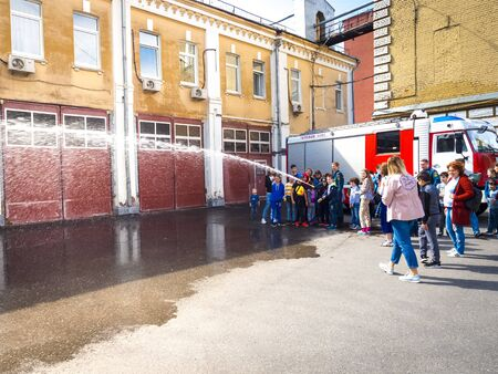 MOSCOW, RUSSIA - AUGUST 07, 2019: Fire station. Side view of children and parents at a fire station trying a fire hose and sprays water, assisted by a fireman Редакционное
