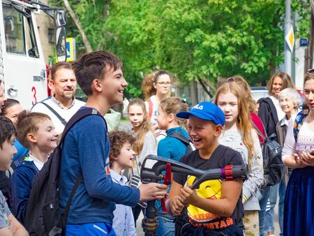 MOSCOW, RUSSIA - AUGUST 07, 2019: Happy kids acting like a fireman holding firehose nozzle and splashing water.Child in a school group of children and adults with hose in hands playing firefighter. Редакционное