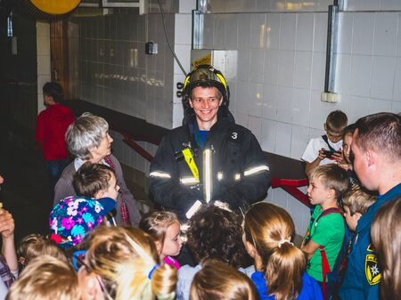 MOSCOW, RUSSIA - AUGUST 07, 2019: Fire station. A fireman explaining his job to children. Excursion for students at the fire station Редакционное