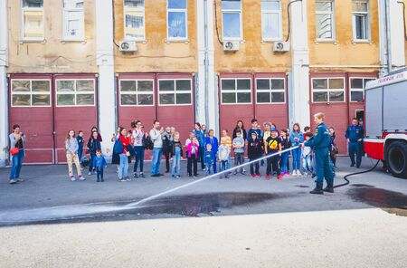 MOSCOW, RUSSIA - AUGUST 07, 2019: Fire station. A fireman explaining his job to children. fire hose lets powerful water jets