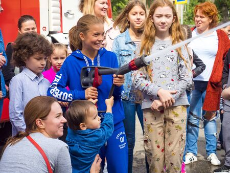 MOSCOW, RUSSIA - AUGUST 07, 2019: Fire station. Happy kids acting like a fireman holding firehose nozzle and splashing water.Child with hose in hands playing firefighter.