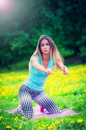 Smiling brunette woman stretching outdoor on the grass Stock Photo