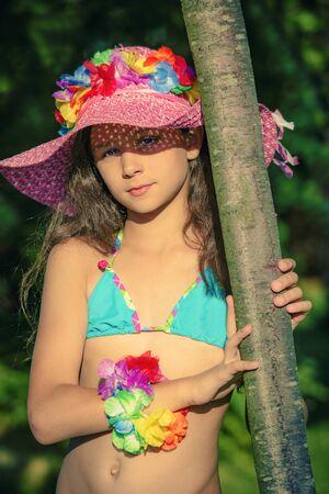 Schönes kleines Mädchen in einem blauen Badeanzug und Hut steht an einem warmen Sommertag in der Nähe eines Baumes. Schönes Porträt eines kleinen Kindes.