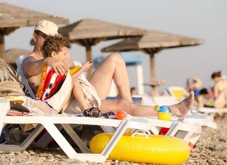 Mature dad and little son sitting on sunbeds sunbathing on beach 版權商用圖片