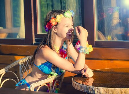 Girl in a swimsuit on the beach near the bungalow. Attractive young girl Sitting on the chair at a table in a bungalow