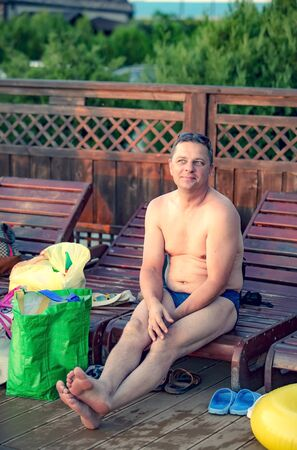 A mature man dressed in edits sitting on a lounger near bags with things of his family. Parental care concept.