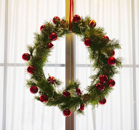 Christmas wreath on the window. Wreath decorated on the window of the room Stock Photo