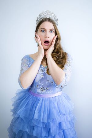 Portrait of a shocked girl wearing crown while looking at camera isolated over light background