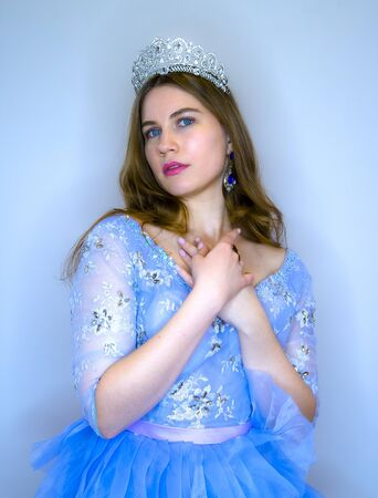 Young beautiful girl with blue eyes in a blue festive dress. Girl with a crown as princess.