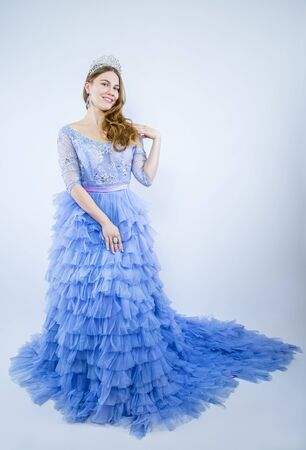 Full Length of blue-eyed brown-haired in blue Evening Ball Gown dress with Silver Diamond Crown Sash, fashion make up face hair style, studio lighting light background isolated copy space