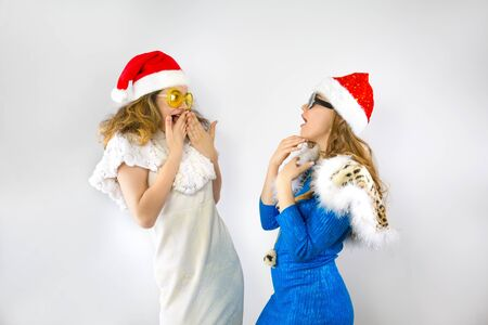 Shocked young Santa couple friends girls in Christmas hat posing isolated on pastel light background in studio. Happy New Year 2020 celebration holiday concept. Mock up copy space.