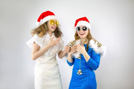 Happy laughing women in Santa hats having fun isolated on gray backdrop Happy New Year 2020 celebration holiday concept. Mock up copy space.