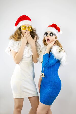 Shocked young Santa couple friends girls in Christmas hat posing isolated on gray background in studio. Happy New Year 2020 celebration holiday concept. Mock up copy space.