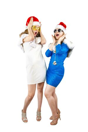 Wow. Portrait of two shocked amazed excited girlfriends in red santa hats. Isolated on white 版權商用圖片