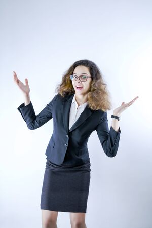Beautiful smiling positive business woman in glasses looking and pointing palms up on copy space background. Closeup portrait