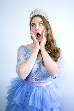 Portrait of a shocked girl wearing crown while looking to the side isolated over light background