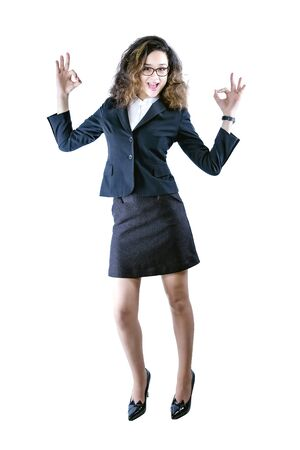 Young beautiful business woman wearing glasses over isolated background success sign doing positive gesture with hand, smiling and happy. Looking at the camera with cheerful expression, win 版權商用圖片