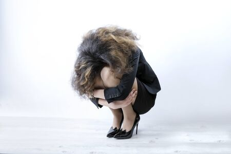 Thoughtful sad depressed curly pretty business woman bowing her head to her knees sitting squatting. Copy space. Despair concept.