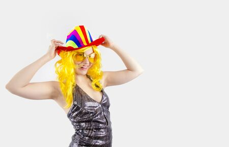 A young lady in a multi-colored carnival cowboy hat, carnival glasses is looking at the camera. Isolated on a gray background. Copy pace Reklamní fotografie