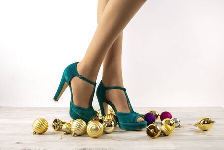 Slender female legs in fashionable turquoise sandals with among Christmas toys on a light background, close-up. Preparing for the holidays. Concept of fashion and elegance