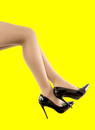 Slender female legs in fashionable black patent leather shoes with narrow socks on a yellow background. Side view