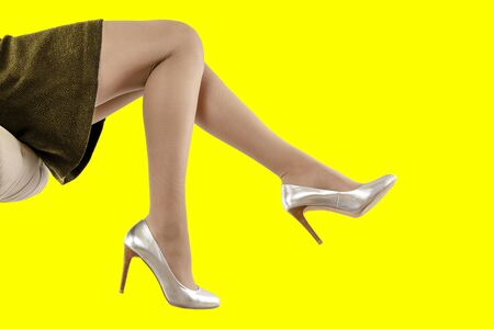 Slender female legs in fashionable silver high heel shoes on a yellow background. Side view