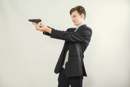 gunman ready to shoot, light background. Portrait shot of a man in a suit aiming with a gun. Copy space