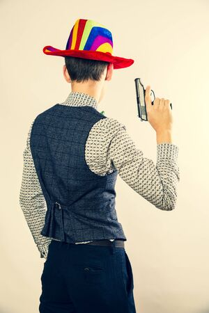Funny handsome man with a gun as a cowboy in carnival. Back view