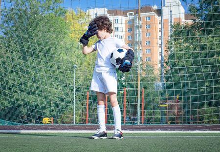 Letni turniej piłki nożnej dla małych dzieci. Klub piłkarski. emocje i radość z gry. Młody bramkarz. Dzieci - mistrz piłki nożnej. Chłopiec bramkarz w sportowej piłki nożnej na stadionie z piłką. Koncepcja sportu.