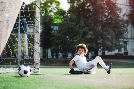 Children's soccer football - a match of young children on the football field. Young goalie. Kids - soccer champion. Boy goalkeeper in football sportswear on stadium with ball. Sport concept. 版權商用圖片