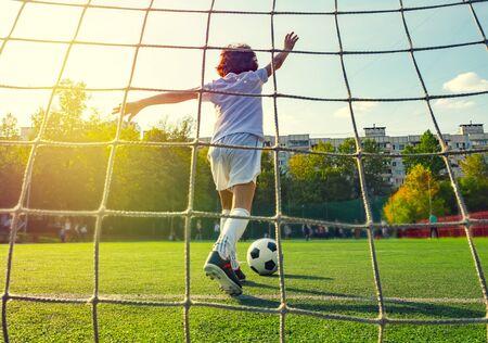 Letni turniej piłki nożnej dla małych dzieci. Klub piłkarski. Młody bramkarz. Chłopiec bramkarz w sportowej piłki nożnej na stadionie z piłką. Koncepcja sportu. Kopnięcie od bramki. Widok z tyłu siatki