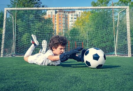 Young soccer goalie attempting to make a save. little soccer goalkeeper with gloves. Kids - soccer champion. Boy goalkeeper in football sportswear on stadium with ball. Sport concept. Selective focus. Stockfoto