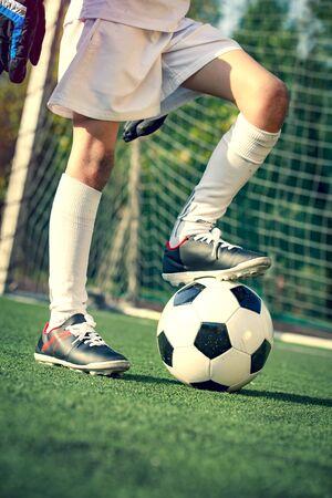 Soccer, football kick off. Man controls a soccer ball on the grass. Summer soccer tournament for young kids. Boy goalkeeper in football sportswear on stadium with ball. Sport concept. 版權商用圖片