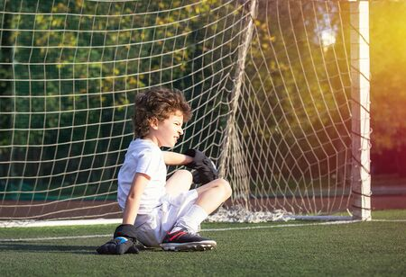 Children's soccer football - a match of young children on the football field. Thoughtful little boy sitting on the green grass in the goalposts. Boy goalkeeper in football sportswear on stadium.