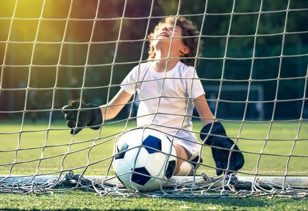 Summer soccer tournament for young kids. football club. emotions and joy of the game. Young goalie. Kids - soccer champion. Boy goalkeeper in football sportswear on stadium with ball. Sport concept.