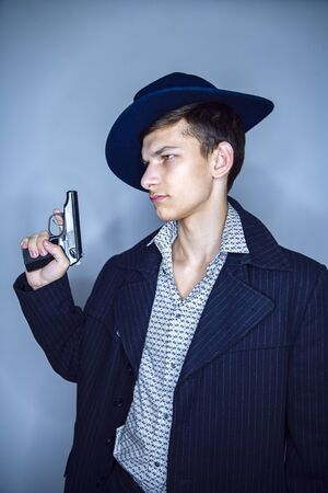 Young assassin in hat holding his gun and looking thoughtfully away from the camera