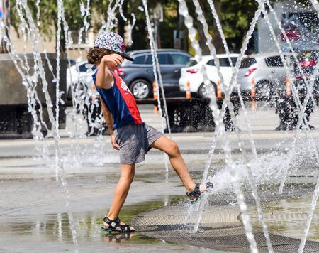 Happy kid playing in a fountain with water. Child having fun with water on sunny summer day. Active leisure for kids.