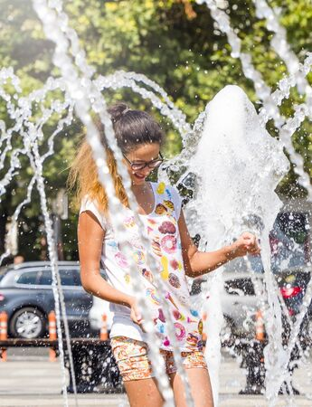 A laughing teenager girl dances happily in a summer fountain in Krasnodar. welcome summer. Strong heat in the city: girl playing with fountain water jets at the square. Standard-Bild