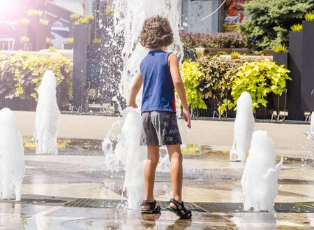 Child playing with water at street fountain in summer. Little boy playing in a fountain