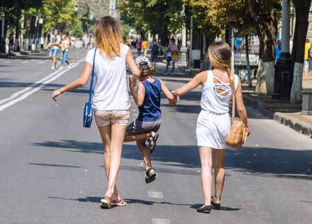 A boy walks with his older sisters on the street on a warm summer day. Expression of love and support for sisters to little. Love between mother, daughter and son.