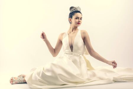 beautiful very young bride with big bust in a luxurious wedding dress and tiara. Copy space