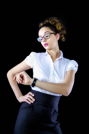 Elegant pretty young business woman in white shirt posing isolated on black background studio portrait. Achievement career wealth business concept. Mock up copy space. Looking on smart watch on hand