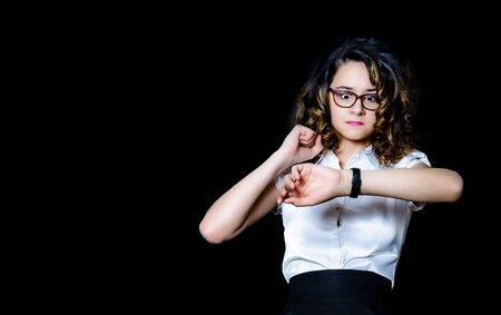 Portrait of a shocked young businesswoman wearing formal suit and glasses standing isolated over black background, looking at wrist watch. Copy space