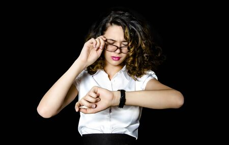 Portrait of a shocked young businesswoman wearing formal suit and glasses standing isolated over black background, looking at wrist watch