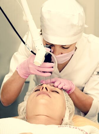 Doctor cosmetologist makes the procedure using professional laser system to an adult woman patient. Laser resurfacing and face treatment