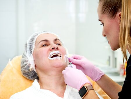 Mature woman at a beautician appointment. applying anesthetic cream to the lips.